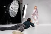 """Постер, картина, фотообои """"фотограф, лежа и стрельба красивая женская модель в фото студии"""""""