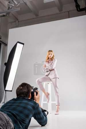 Photo for Photographer with camera lying and photographing beautiful female model posing in studio - Royalty Free Image