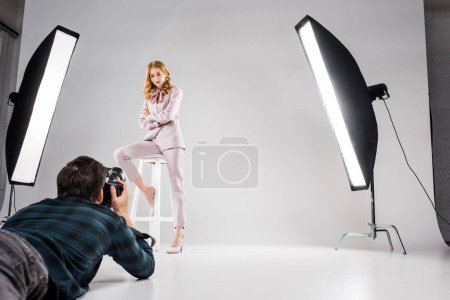 young photographer with camera lying and photographing beautiful female model posing in studio