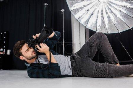 Photo pour Beau jeune photographe couché et utilisant un appareil photo en studio - image libre de droit