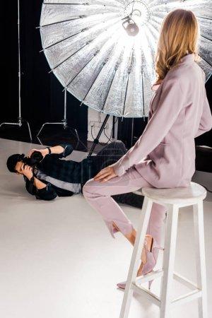 Photo pour Jeune photographe avec caméra couché et photographier le beau modèle en studio - image libre de droit