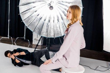 Photo pour Belle jeune mannequin posant et mâle photographe avec caméra couché et photographier en studio - image libre de droit