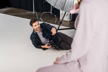 Photo pour Vue grand angle du photographe souriant avec caméra couché et de travailler avec un modèle féminin en studio - image libre de droit