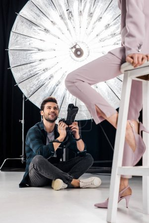 Photo for Cropped shot of smiling photographer sitting and photographing stylish model in studio - Royalty Free Image