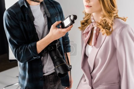 cropped shot of young photographer holding light meter and working with female model in studio
