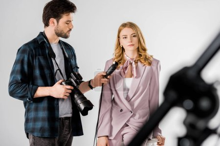 young photographer holding camera and light meter while working with model in studio