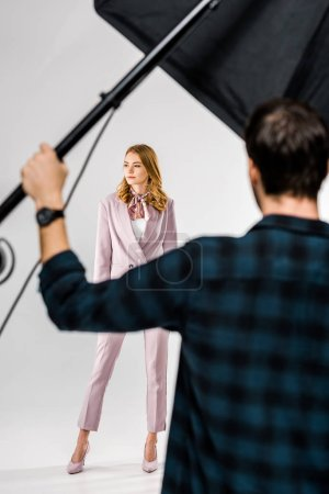 back view of photographer working with lighting equipment while female model posing in studio