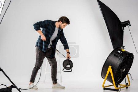 Photo pour Jeune homme travaillant avec de l'équipement dans un studio photo professionnel - image libre de droit