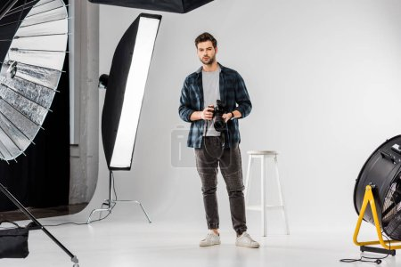 handsome young photographer holding professional camera and looking at camera in photo studio