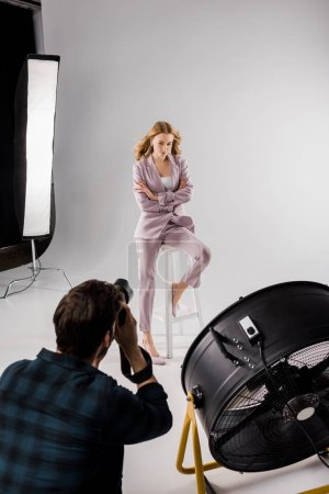 high angle view of young photographer shooting beautiful young woman in photo studio