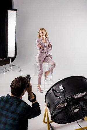 Photo pour Vue d'angle élevé du jeune photographe tournage beau modèle féminin en studio - image libre de droit