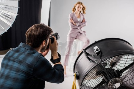 young photographer shooting beautiful stylish young female model posing in photo studio