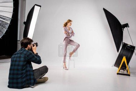 Photo pour Mâle belle élégante jeune femme photographe en studio photo - image libre de droit