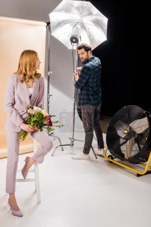 Photo pour Jeune photographe travaillant avec des équipements d'éclairage et regardant beau modèle féminin avec des fleurs en studio photo - image libre de droit