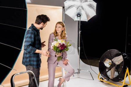 Foto de Fotógrafo joven alegre y hermosa mujer modelo en estudio fotográfico - Imagen libre de derechos