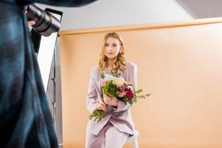 Photo pour Recadrée tir du jeune modèle féminin avec des fleurs dans le studio photo photographe - image libre de droit