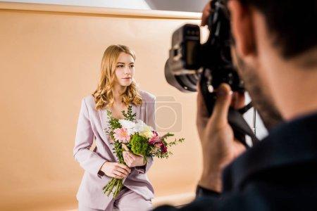 Photo pour Recadrée tir du photographe prise de vue belle jeune modèle féminin avec des fleurs en studio photo - image libre de droit