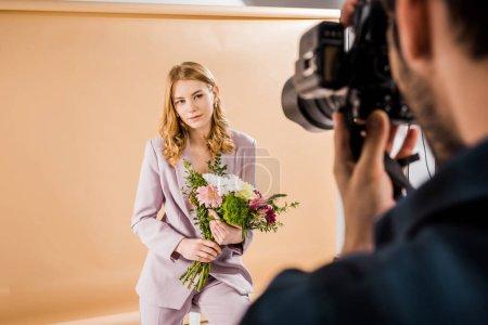 Photo pour Recadrée tir du photographe prise de vue belle jeune modèle féminin avec bouquet de fleurs en studio - image libre de droit