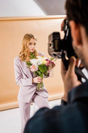 Photo pour Recadrée tir du jeune modèle féminin posant avec fleurs en studio photo photographe - image libre de droit