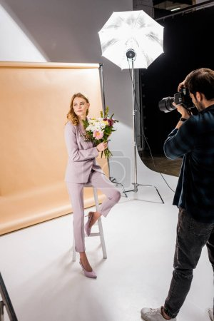 Photo for Photographer shooting attractive young female model posing with flowers in photo studio - Royalty Free Image