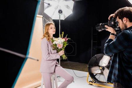 Photo pour Belle jeune femme posant avec fleurs en studio photo photographe - image libre de droit