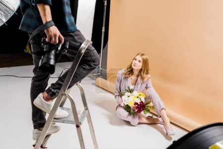 Photo pour Plan recadré de photographe debout sur l'échelle tandis que la femme attrayante posant avec bouquet en studio - image libre de droit