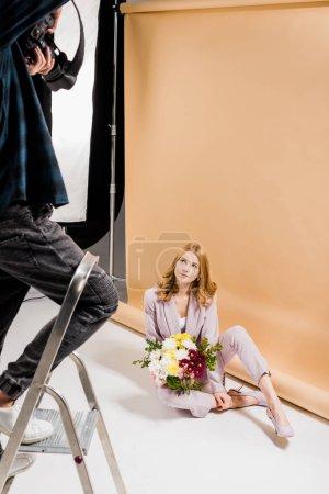 Photo pour Recadrée tir du photographe debout sur l'escabeau et belle fille avec des fleurs de prise de vue en studio - image libre de droit