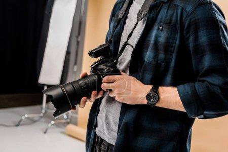 Photo pour Recadrée tir du jeune photographe qui tient l'appareil-photo en studio photo - image libre de droit