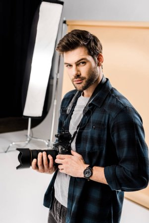 handsome young photographer looking at camera in professional photo studio