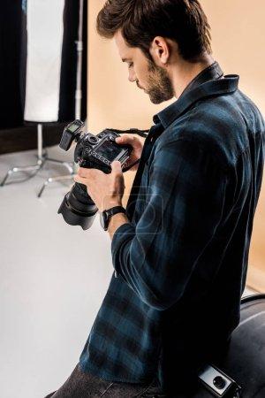 Photo pour Beau jeune photographe à l'aide de caméra en studio photo - image libre de droit