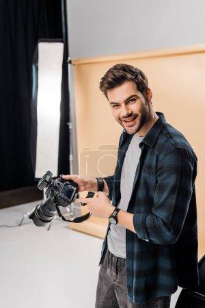 Photo pour Beau jeune photographe heureux pointant à la caméra en studio photo - image libre de droit