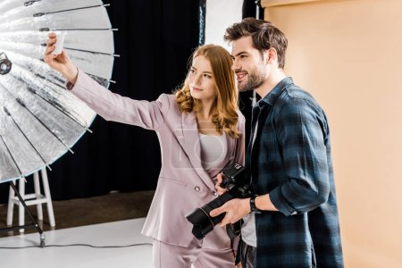 Photo for Handsome young photographer and beautiful smiling model taking selfie with smartphone in photo studio - Royalty Free Image