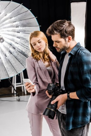 Photo for Photographer with camera and beautiful female model using smartphone in photo studio - Royalty Free Image