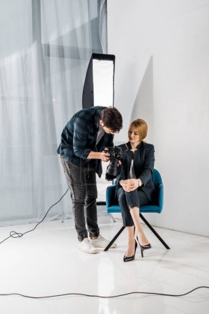 Photo for Photographer showing camera to beautiful young woman in photo studio - Royalty Free Image