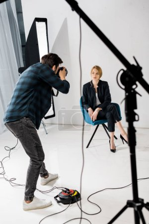 young man photographing beautiful female model in photo studio
