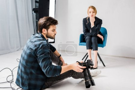 Photo for Young photographer showing camera to beautiful female model in photo studio - Royalty Free Image