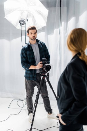 handsome young photographer standing with camera and looking at beautiful model in photo studio