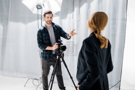 Photo for Smiling young photographer using camera and talking with female model in studio - Royalty Free Image