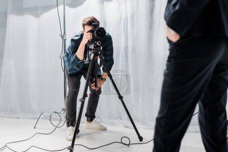 Photo pour Recadrée tir du jeune photographe tournage beau modèle féminin en studio photo - image libre de droit