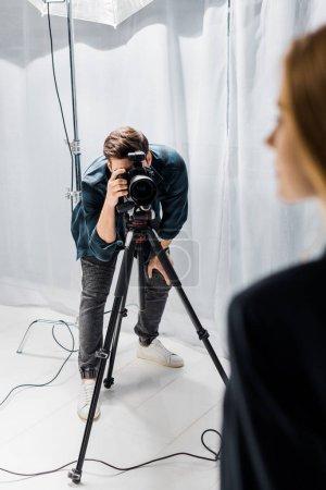 Photo pour Recadrée tir du jeune photographe tournage beau modèle féminin en studio - image libre de droit