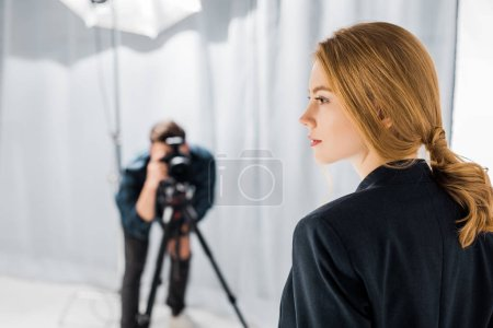 Photo pour Vue rapprochée du beau jeune mannequin et photographe travaillant derrière en studio - image libre de droit