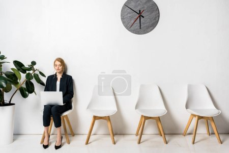 Photo for Young businesswoman using laptop while sitting on chair and waiting in line - Royalty Free Image
