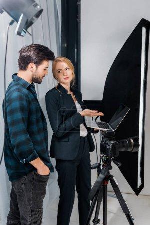 Photo pour Photographe et modèle à l'aide d'ordinateur portable et regardant les uns les autres en studio photo - image libre de droit