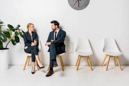 Photo pour Jeunes gens d'affaires détenant les gobelets en papier et en regardant les uns les autres en attendant sur des chaises en ligne - image libre de droit