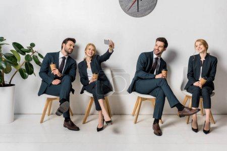 Foto de Collage de sonrientes jóvenes empresarios con smartphone y papel tazas esperando en las sillas en línea - Imagen libre de derechos