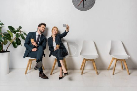 Photo for Smiling business people taking selfie with smartphone while sitting on chairs in line - Royalty Free Image
