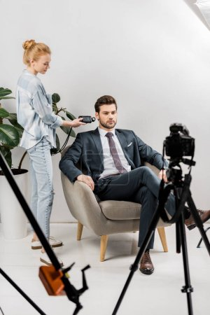 young photographer using light meter while working with handsome businessman in studio