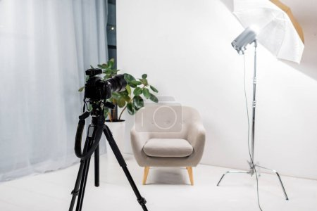 close-up view of professional photo camera on tripod, empty armchair and lighting equipment in studio