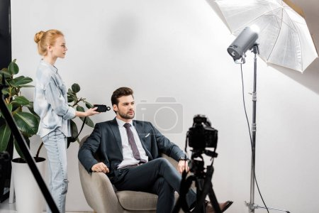 young photographer using light meter while working with handsome male model in studio