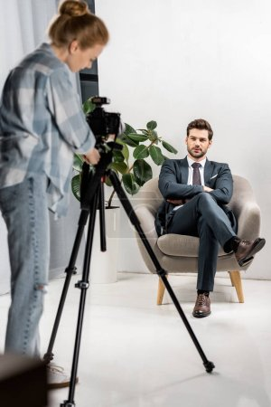 young photographer taking pictures of handsome male model in studio